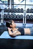 Concentrated fit woman doing sit ups. At gym Royalty Free Stock Photography