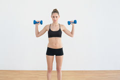 Concentrated fit woman lifting blue dumbbells Stock Photography
