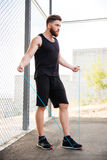 Concentrated fitness man doing cardio exercises with skipping rope outdoors Stock Images