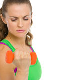 Concentrated fitness young woman making exercise with dumbbells Stock Image
