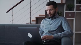 Man using laptop computer and working distant sitting at home. Concentrated, focused and busy man in formal wear clothes sitting on cozy and comfort sofa in stock video