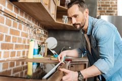 Concentrated focused man estimating length. Accurate measurement. Serious earnest pretty man leaning over surfaces while holding roulette and measuring Royalty Free Stock Photography