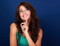 Concentrated fun grimacing woman thinking and looking up on empt Stock Photos