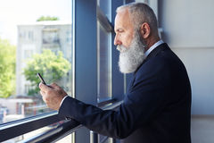 Concentrated gentleman surfing in phone while leaning on handrai Royalty Free Stock Photo