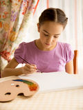 Concentrated girl drawing on canvas by oil paints Stock Images