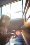 Concentrated girl looking at digital tablet while practicing piano Royalty Free Stock Image