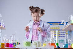 Concentrated girl looks at evaporation of reagent Stock Photos