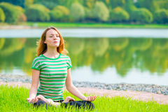 Concentrated girl in lotus position doing yoga Stock Photo
