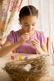 Concentrated girl painting Easter eggs at table Stock Photos