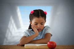 Composite image of concentrated girl reading book at desk. Concentrated girl reading book at desk against room with large windows Stock Photo