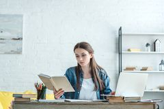 concentrated girl reading book and using laptop while studying royalty free stock photo