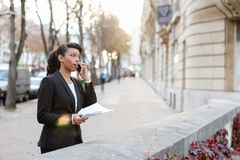 Concentrated girl talking on mobile, young business woman negoti stock photography