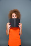 Concentrated girl with voluminous curly hairstyle reading a book Stock Images