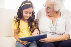 Concentrated granddaughter using tablet with grandmother Stock Images
