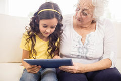 Concentrated granddaughter using tablet with grandmother Stock Image