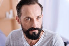 Concentrated grey-eyed man of middle age. Being concentrated. Serious bearded dark-haired man of middle age having grey eyes and wearing a white shirt and Stock Photography