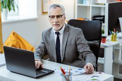 Concentrated grey-haired man in grey strict costume sitting in cabinet. Busy businessman. Concentrated grey-haired man in grey strict costume sitting in cabinet royalty free stock photo