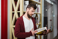 Concentrated guy holding glasses and reading book in library stock photography