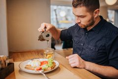 Concentrated guy is pouring some tea into cup. There is a plate of tasty meal on table. Man is preparing to have a. Dinner royalty free stock images