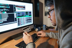 Concentrated hacker in glasses stealing money from diferent credit cards Royalty Free Stock Photo