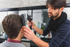 Concentrated hairdresser doing hairstyle with hairdryer Royalty Free Stock Photo