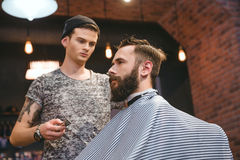 Concentrated hairdresser making haircut to bearded handsome man at barbershop Stock Image