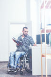 Concentrated handicap enjoying reading book indoors. Looking for inspirational quotes. Handsome smart young handicap sitting on the wheelchair indoors and Stock Photos