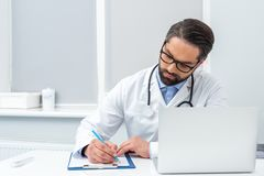 Concentrated handsome doctor writing in clipboard. At workplace Royalty Free Stock Photos