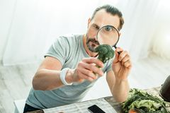 Concentrated handsome man holding a broccoli looking through magnifying glass.