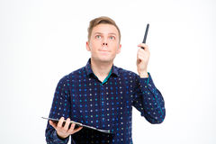 Concentrated handsome man holding clipboard and pointing up by pen Stock Images