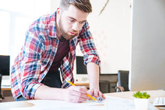 Concentrated handsome man working and drawing blueprint Stock Image