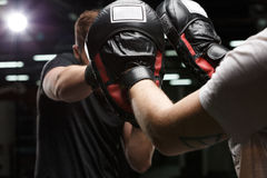 Concentrated handsome young strong sports man boxer. Image of concentrated handsome young strong sports man boxer make exercises in gym with trainer. Focus on royalty free stock photo