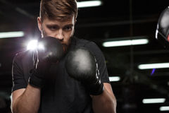 Concentrated handsome young strong sports man boxer. Image of concentrated handsome young strong sports man boxer make exercises in gym with trainer and looking royalty free stock images