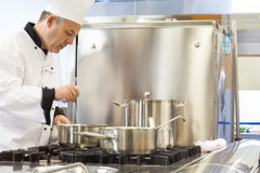 Concentrated head chef stirring in pot Stock Images