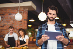 Concentrated hipster using tablet in front of working barista Stock Photography