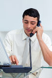 Concentrated Hispanic businessman on phone. At work stock photo