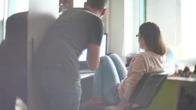 Concentrated indoors couple of young colleagues working in modern office. Two coworkers discussing their work, working. With documents. man and woman working in stock video