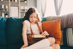 Concentrated kid girl reading interesting book at home Royalty Free Stock Photography