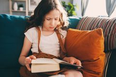 Concentrated kid girl reading interesting book at home. Concentrated kid girl reading interesting fairy tale book at home royalty free stock photos