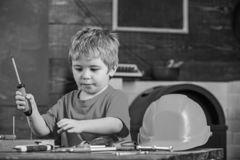 Concentrated kid playing with screwdriver. Cute blond boy learning to work with tools. Little repairman grabbing royalty free stock image