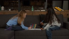 Concentrated kids painting coloring pages at home stock footage