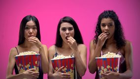 Concentrated ladies attentively watching movie and eating popcorn, pajama party. Stock photo stock photo