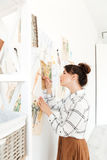 Concentrated lady fashion illustrator drawing. Picture of young concentrated lady fashion illustrator standing near a lot of illustrations and drawing. Looking Stock Images