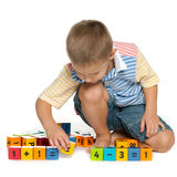 Concentrated little boy with blocks on the floor Stock Images