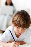 Concentrated little boy drawing lying on the floor Royalty Free Stock Images