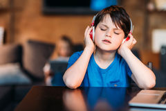 Concentrated little boy listening music in headphones. Portrait of concentrated little boy listening music in headphones stock image