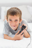Concentrated little boy lying on bed playing video games Stock Image