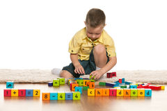 Concentrated little boy with toys on the floor Royalty Free Stock Photography