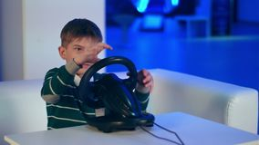 Concentrated little boy playing virtual reality racing game. Professional shot in 4K resolution. 093. You can use it e.g. in your commercial video, business stock video