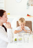 Concentrated little boy praying with his mother Stock Photos
